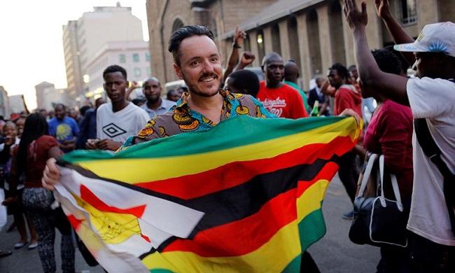 Manifestantes celebran la dimisión de Robert Mugabe como presidente en las inmediaciones del Parlamento en Harare (Zimbabue)